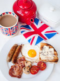 Bacon,  eggs and sausages with cup of tea, teapot, toast and bri. English fried breakfast on a white table top with cup of tea in union jack mug, red teapot Royalty Free Stock Images