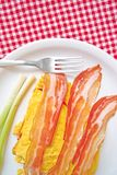 Bacon and eggs. Bacon and scrambled eggs with green leek on white plate served as breakfast. Traditional breakfast with lots of calories Stock Photos