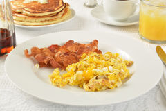 Bacon and eggs. Bacon and scrambled eggs with pancakes and juice Stock Images