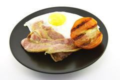 Bacon, Eggs and Tomato on a Black Plate Stock Images