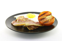 Bacon, Eggs and Tomato on a Black Plate Stock Photos