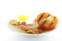 Bacon, Eggs and Tomato on a White Plate Royalty Free Stock Photo