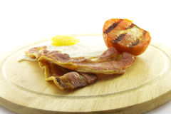 Bacon, Eggs and Tomato on Wooden Plate Stock Image