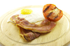Bacon, Eggs and Tomato on Wooden Plate Royalty Free Stock Image