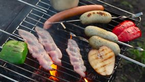 Bacon en worsten op een rozemarijn die van de de vlamgrill van de grillbrand wordt gebraden stock video