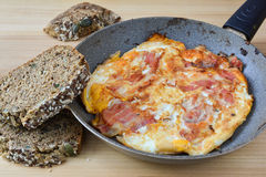 Bacon end eggs with chrono bread. Strong breakfast, fried bacon and eggs in old frying pan and healthy chrono bread with seeds Stock Photography