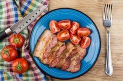 Bacon fritado com os tomates na placa azul, faca no guardanapo Fotografia de Stock