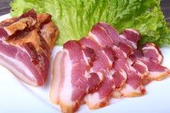 Bacon fumado caseiro fresco com alface de folhas na placa branca Foco seletivo Fotos de Stock Royalty Free