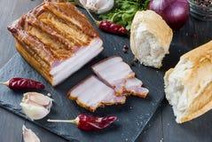 Bacon fumado com baguette e vegetais na placa preta de pedra Fotos de Stock Royalty Free