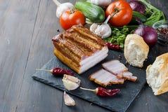 Bacon fumado com baguette e vegetais na placa preta de pedra Imagem de Stock