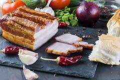 Bacon fumado com baguette e vegetais na placa preta de pedra Imagem de Stock Royalty Free