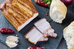 Bacon fumado com baguette e vegetais na placa preta de pedra Foto de Stock