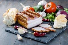 Bacon fumado com baguette e vegetais na placa preta de pedra Imagens de Stock