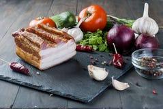 Bacon fumado com os vegetais na placa preta de pedra Imagens de Stock Royalty Free