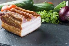 Bacon fumado com os vegetais na placa preta de pedra Fotos de Stock