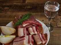 Bacon  and  glass of vodka. Lard, bread, a glass of vodka, onions Stock Photos