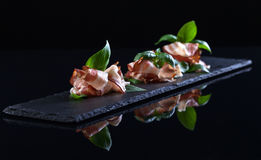 Bacon with green basil on a black background Stock Photo