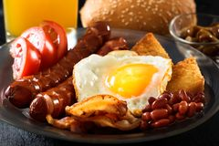 Bacon, grilled sausages, fried egg, beans, beans, toast, tomatoes, mushrooms fresh juice - full English breakfast stock photo