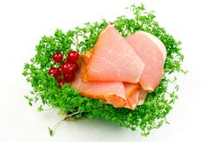 Bacon hamon delicacy with springs of salad isolated. On white stock image