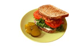 A bacon, lettuce and tomato sandwich with pickles isolated on wh Stock Photos
