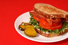 Bacon, lettuce and tomato sandwich with pickles, red background Stock Photo