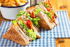 Bacon lettuce tomato sandwich with spring onion mayo and fries.  Royalty Free Stock Photography