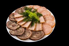 Bacon, meat roll and sausage, decorated with salad and dill on a black background royalty free stock photography