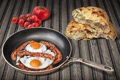 Bacon och ägg som är förberedda i gamla steka Pan Set On Rustic Bamboo Mat With Torn Pitta Bread och grupp av mogna Cherry Tomato Royaltyfria Foton