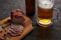 Bacon och exponeringsglas av öl på en tabell Arkivfoto