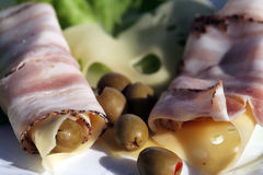 Bacon olives cheese and lettuce. On the plate Royalty Free Stock Photos
