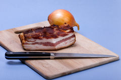 Bacon and onion. Bacon,knife and onion and wooden board Stock Image