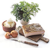 Bacon, onion, cheese and dill. Bacon, on wooden board, knife, onion, cheese, dill and parsley leaves Stock Photography