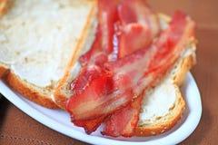 Bacon op beboterd brood stock foto's