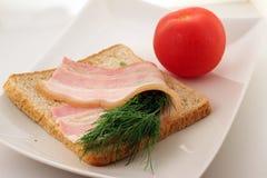 Bacon på en skiva av bröd Arkivfoton