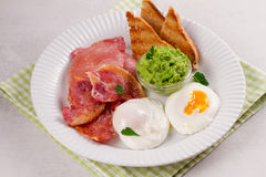 Bacon, poached eggs, mashed peas and toasts on white plate. Grilled rashers and eggs. Stock Photo