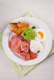 Bacon, poached eggs, mashed peas and toasts on white plate. Grilled rashers and eggs. Royalty Free Stock Images