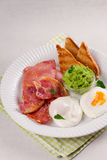 Bacon, poached eggs, mashed peas and toasts on white plate. Grilled rashers and eggs. Stock Image