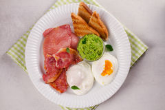 Bacon, poached eggs, mashed peas and toasts on white plate. Grilled rashers and eggs. Royalty Free Stock Photos