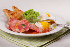 Bacon, poached eggs, mashed peas and toasts on white plate. Grilled rashers and eggs. Stock Photography