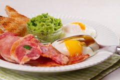 Bacon, poached eggs, mashed peas and toasts on white plate. Grilled rashers and eggs. Stock Photos