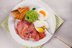 Bacon, poached eggs, mashed peas and toasts on white plate. Grilled rashers and eggs. Royalty Free Stock Photo