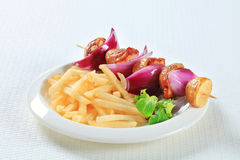 Bacon and potato skewer with fries Royalty Free Stock Photography