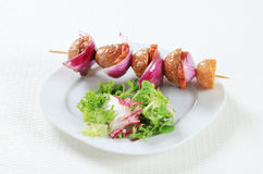 Bacon and potato skewer with salad greens Stock Images