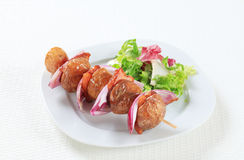 Bacon and potato skewer with salad greens Stock Photos