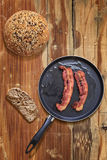 Bacon Rashers in Frying Pan with Bread Slice and loaf on old obsolete Wooden Table Royalty Free Stock Photo