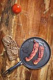 Bacon Rashers in Frying Pan with Bread Slice and Tomato on old obsolete Wooden Table Stock Photos