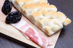 Bacon rolls with prunes and focaccia on cutting board Stock Images