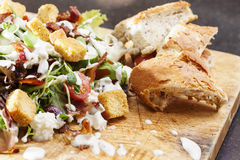 Bacon Salad. Salad served with succulent pieces of British back bacon. Presented on a wooden board with rustic bread stock image