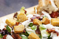Bacon Salad. Salad served with succulent pieces of British back bacon. Presented on a wooden board with rustic bread royalty free stock photos
