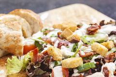 Bacon Salad. Salad served with succulent pieces of British back bacon. Presented on a wooden board with rustic bread stock photography